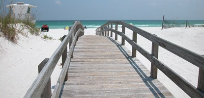 A gray wooden boardwalk crosses over the white sand dunes to the gulf beach.