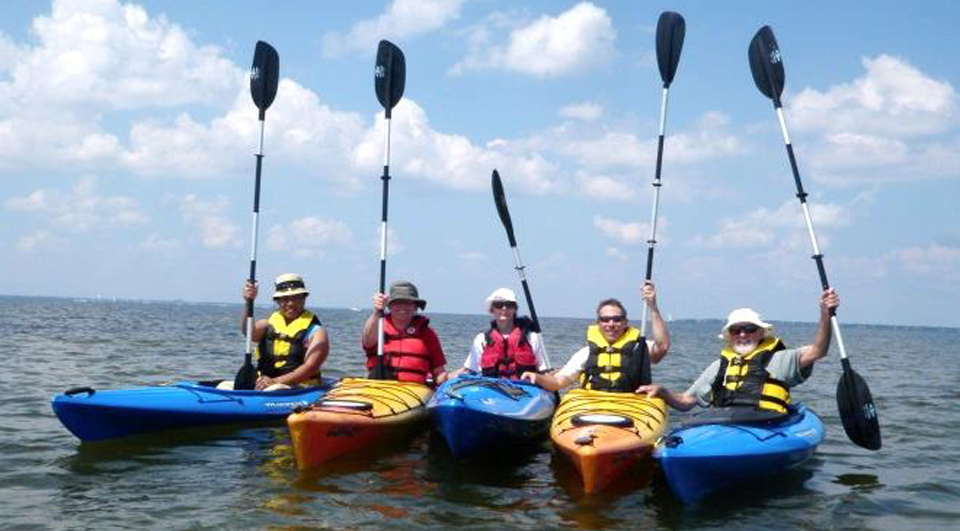 Five kayakers hold their paddles straight up while in the water.