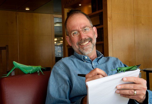 A picture of Jeffrey Lockwood writing on a notepad with some toy grasshoppers for some inspiration.