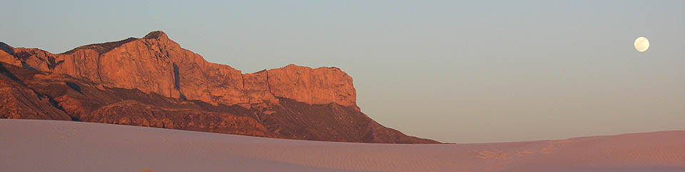 The Western Escarpment of the Guadalupes rises above the white gypsum sands of the desert floor.