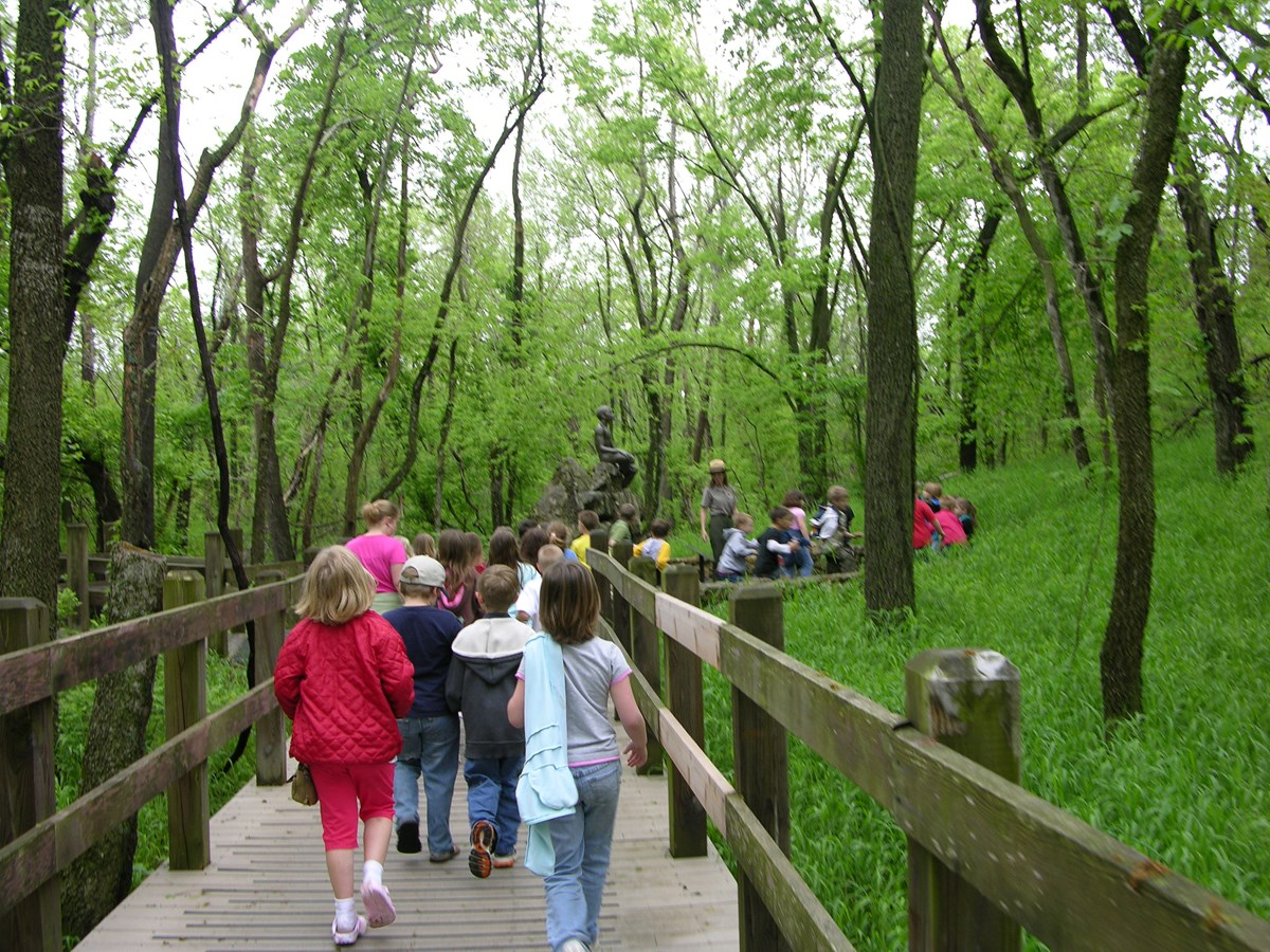 School children on the Carver trail during a field trip. A park ranger is leading the group. Also in the image is a bronze statue of young George Washington Carver.