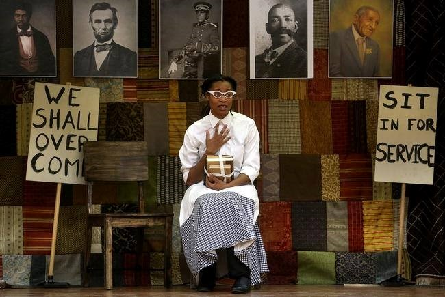 The image is of a play about African American history in the Midwest. The female actor is wearing period clothing of the 1950s. She is sitting on a bench with school books.