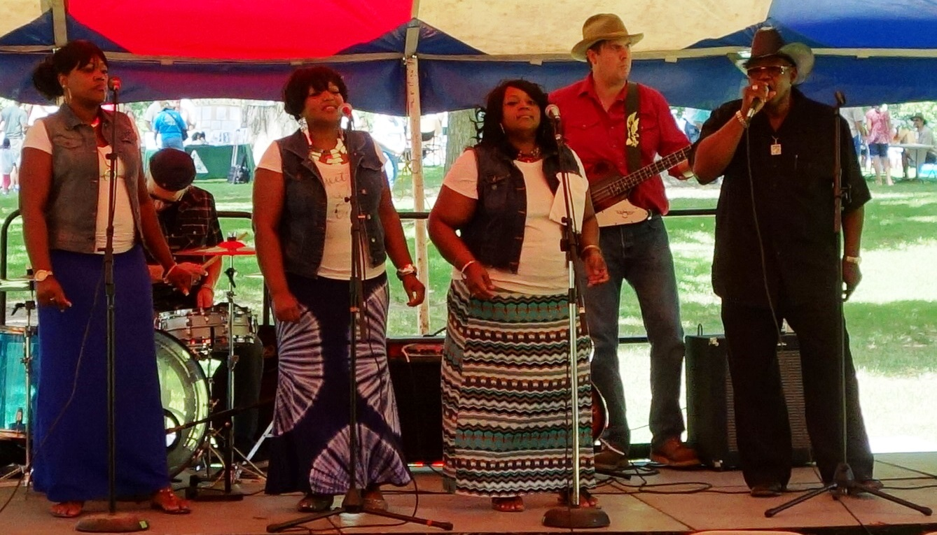 Image is a music group performing at Carver Day. The image includes 3 woman and two men singing under a tent.
