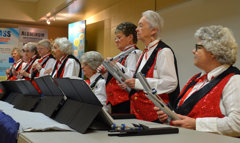 Eights ladies in red vests, playing hand bells.