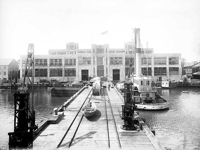Cranes and tug boats wait for freshly made torpedos at the Torpedo Factory dock