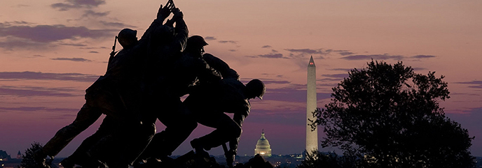Large bronze statue of six men raising a US flag with sunset and Washington, DC in the background