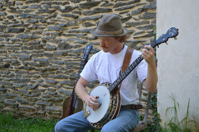 man sitting outside in front of a stone wall playing banjo