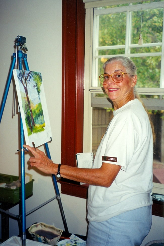 woman stands in front of her easel and in progress painting, indoors next to a window. She is turned toward the camera smiling.