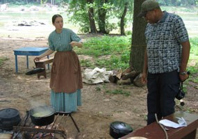 Vanessa Smiley welcomes a visitor to her cooking fire at the Farmer's Market living history program.