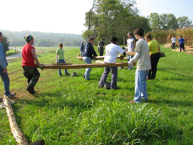 Students from Doane Academy building worm fencing. (NPS PHOTO)