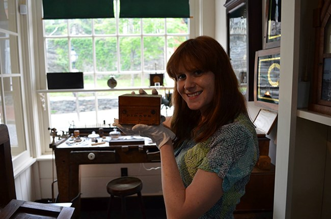 Museum Management intern, Emily, with her favorite artifact in the Burton Jewelry Store exhibit