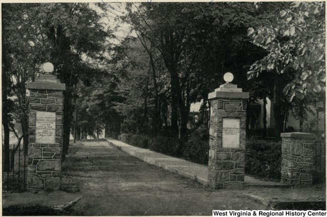 black and white photo of stone pillars, gateway and path