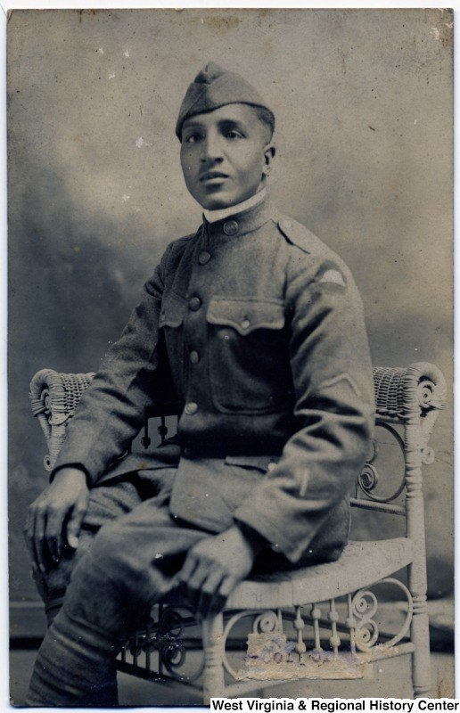African American man seated, posing in a photography studio, wearing his WWI military uniform