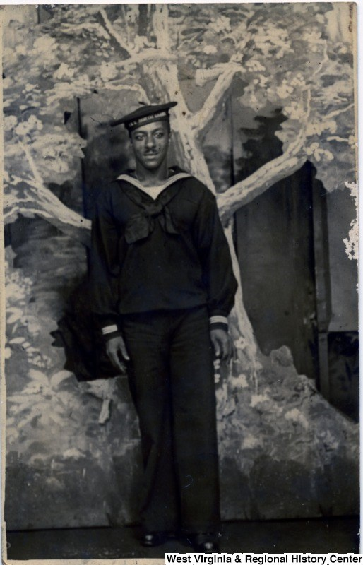 African American man posing in a photography studio, wearing his World War I navy uniform
