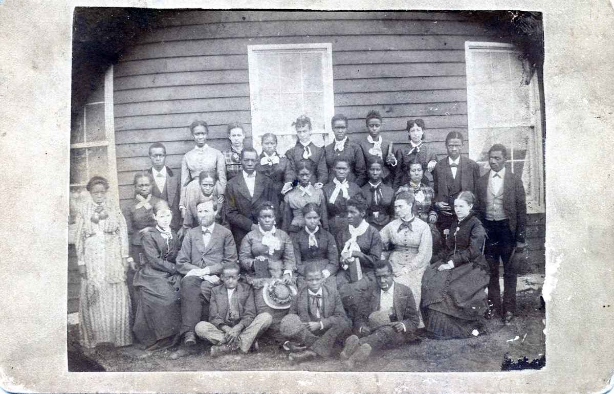 a black and white image of mostly young African Americans seated and standing in front of a board building; white teachers are seated in the group