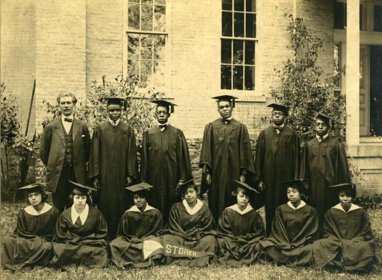 students and principal of Storer; students in graduation attire; seven female students sit on the ground; six males students and the principal stand in a row behind the women