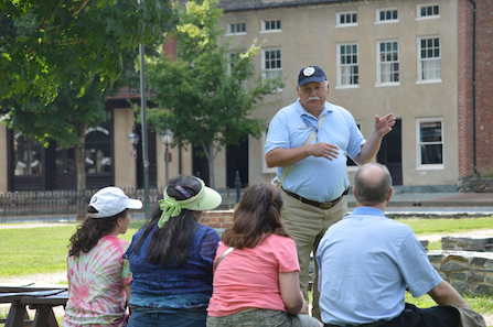 Harpers Ferry Park Guide Jim Prentice giving a tour for a family group.