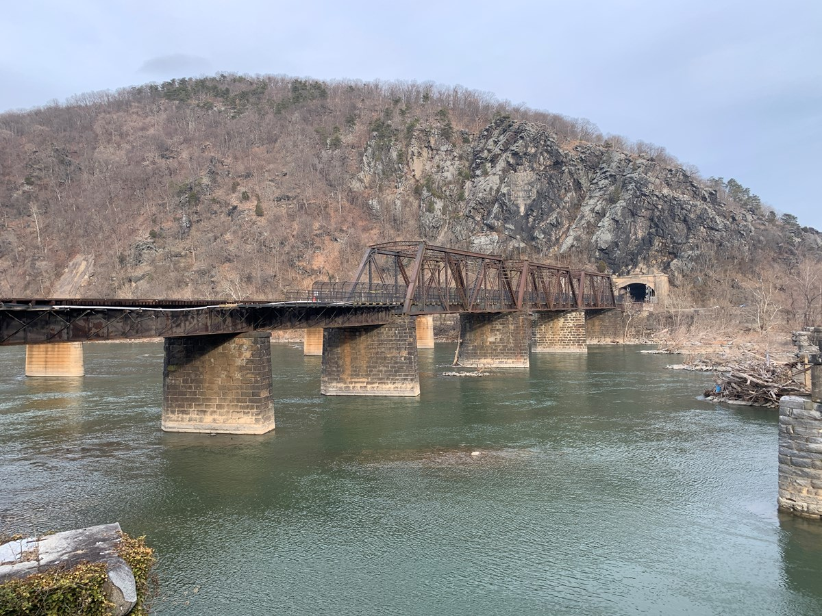 railroad and footbridge over the potomac river; part of the footbridge is gone; Maryland Heights mountain in the background