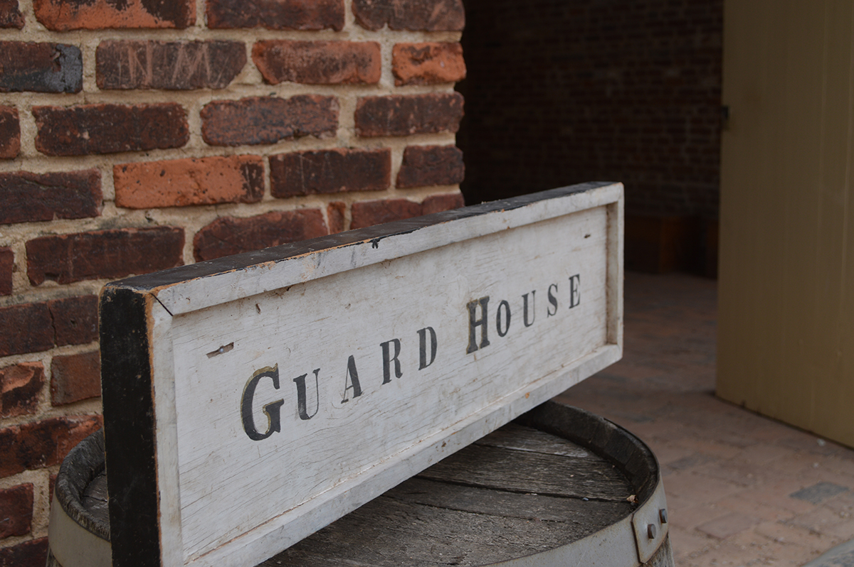 "signs that reads ""Guard House"" atop a barrel in front of a brick building"