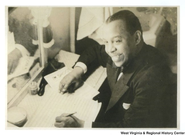 African American man sitting, smiling, with pen and paper in hand