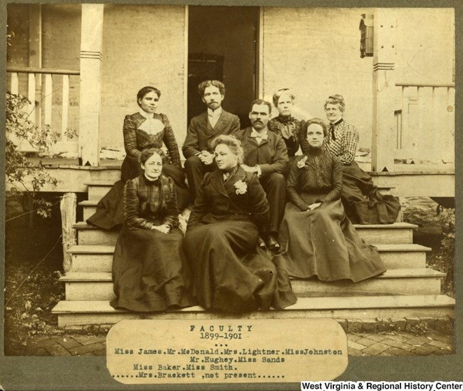 early 1900s image of six women and two men sitting on the steps of a building