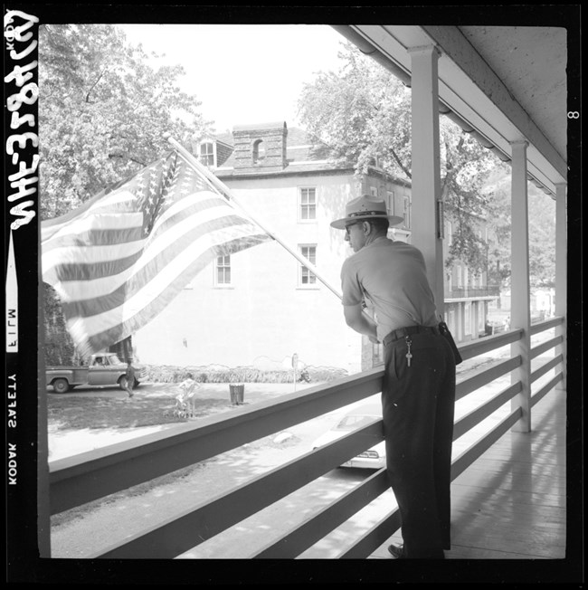 black and white photo of a ranger putting a flag out on a balcony