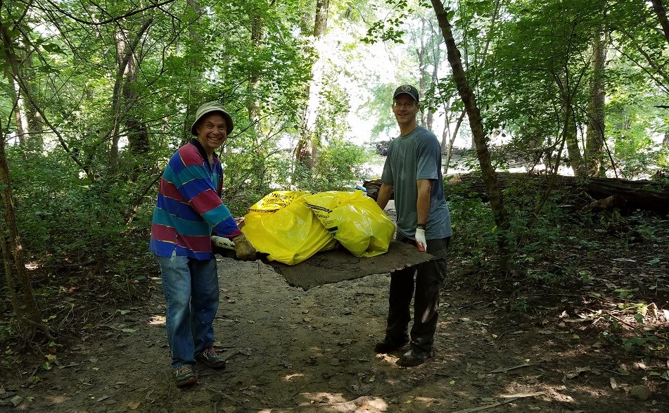 Two smiling volunteers carry trash they have gathered from the banks of the Potomac River