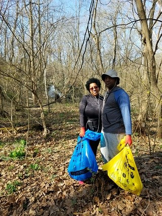Two volunteers hold bags of trash and recycling collected in the park.