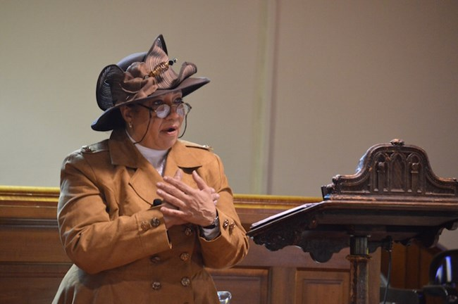 African American woman dressed in early 1900s garb; speaking at a pulpit