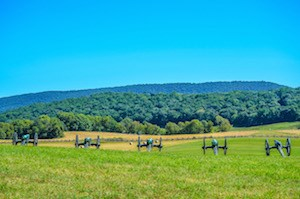a row of five cannons sit in a field pointed toward a distant tree-covered ridge; large hay bails and worm fence are in between the cannons and the ridge