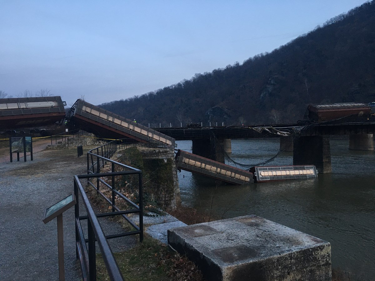 photo of train cars derailed off of a bridge into a river at Harpers Ferry