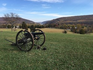 an artillery piece on the fall landscape; in the distance is a gap in the mountains