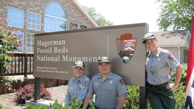 summer uniformed workers near visitor center sign