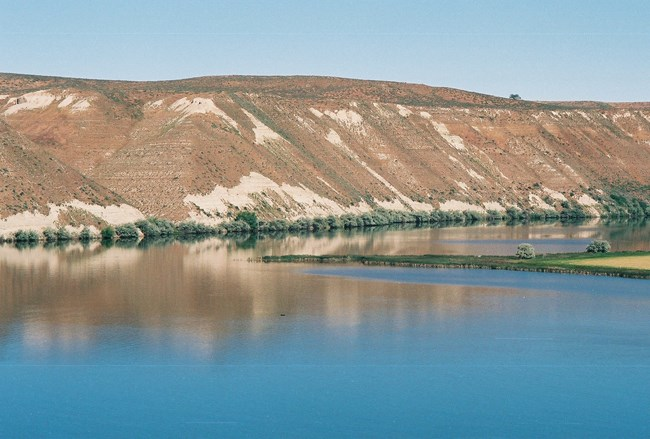 scenic view of fossil bed strata from river