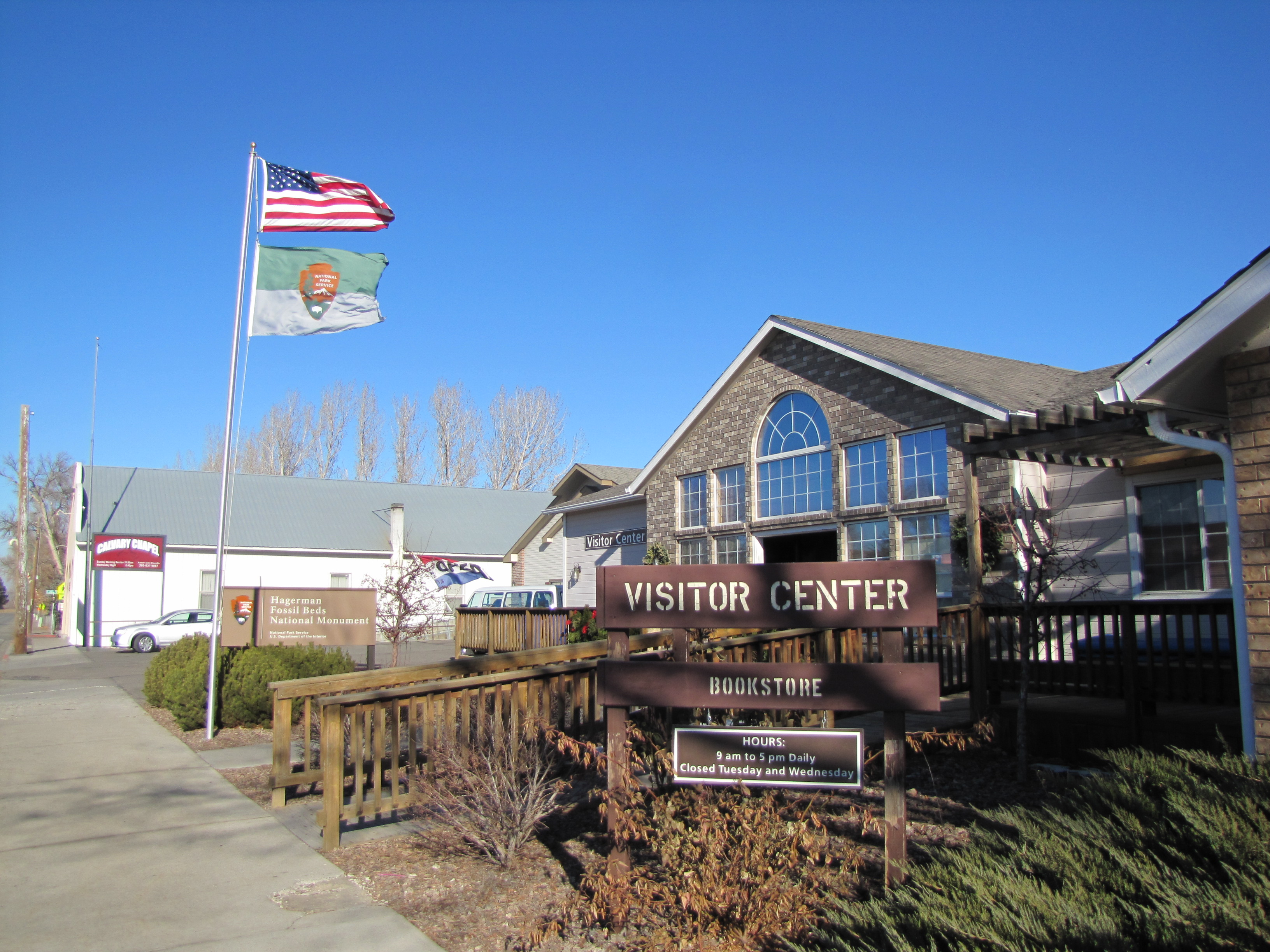 front of the visitor center building with signage and flags