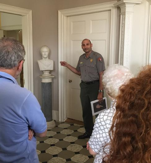 A park ranger discusses a marble bust of Hamilton in the front hall of The Grange.