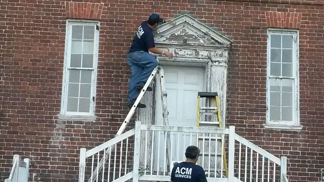 Workers removing lead paint from west side entrance