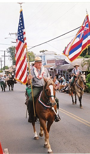 Reeser holding flag at Makawao Parade.