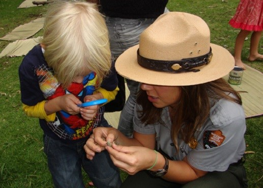 Student looking through a magnifying glass with a ranger.