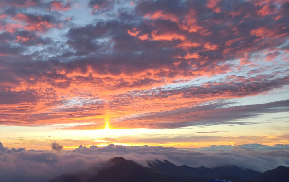 Sun rising between colorful clouds and Haleakala Crater jagged peaks in background