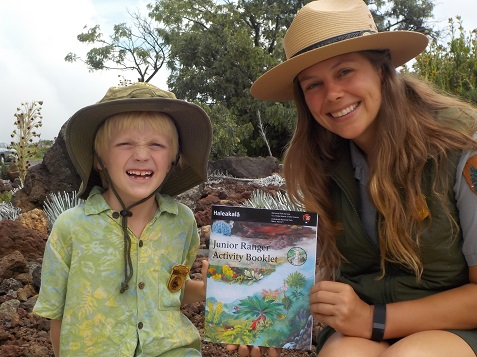 Eliot Carter and Ranger Katelyn Thomson display the park's new Junior Ranger Activity Book.