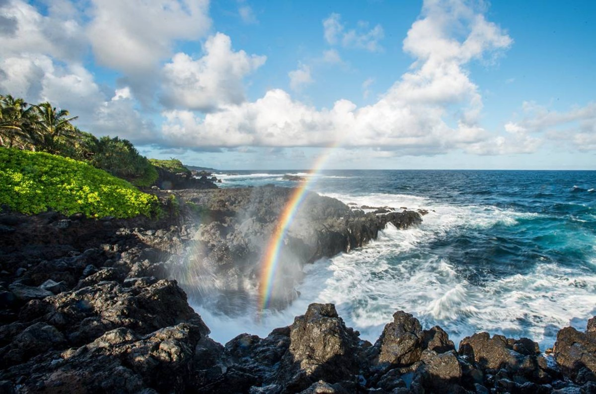 A rainbow forms in the mist of the ocean crashing on a rocky shore.
