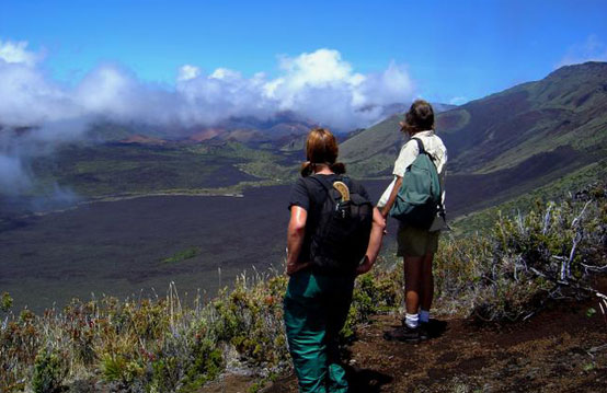 Two hikers look back at the volcanic landscape they have covered on their wilderness hike.