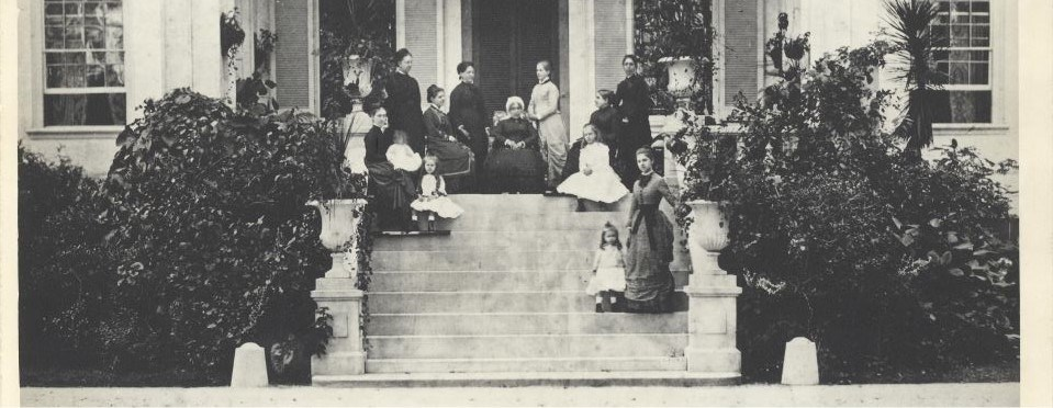 A black and white photograph of women on the front porch of the Hampton mansion.