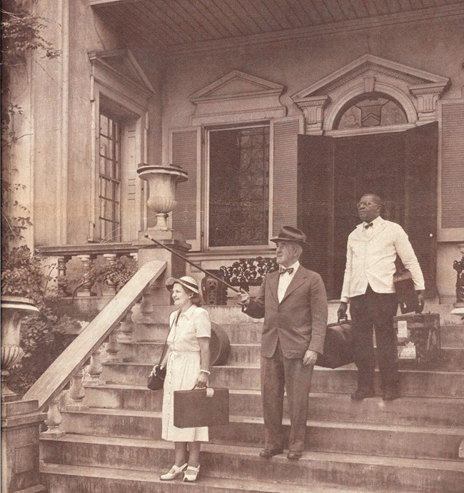 Black and white photograph of John Ridgely Jr. and his wife Jane with a black servant carrying their bags on the front porch of the Hampton mansion.