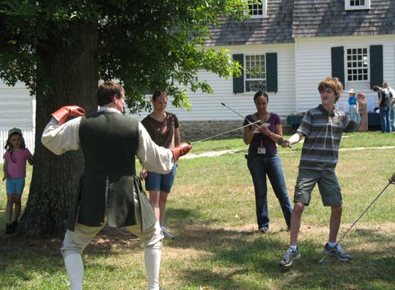A park visitor engages in swordsmanship with an instructor.