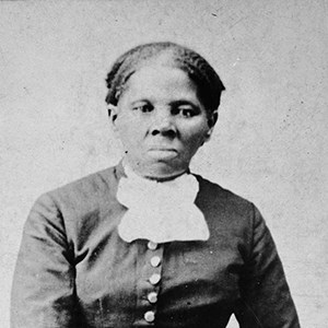 black and white image of African American woman looking at the camera, wearing a dark dress and white collar ruffle