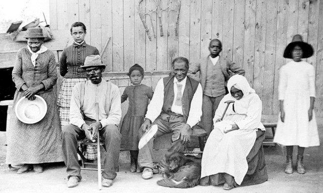 African American family of all ages in front of a house