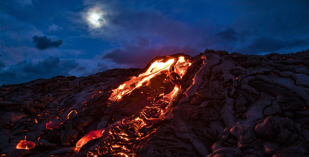 Molten lava underneath a clouded full moon
