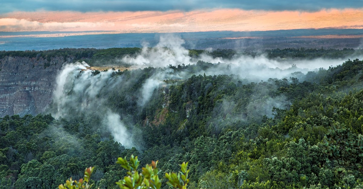Steam rising from the forested edge of a volcanic crater
